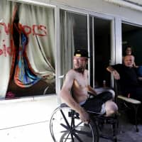 Wes Allen, Jr. sits with his father ,Wes Allen, Sr., sister Alison, and mother, Vicki, outside their room at a damaged motel Tuesday in Panama City, Florida, where many residents continue to live in the aftermath of Hurricane Michael. Many residents rode out the storm and have no place to go even though many of the motel's rooms are uninhabitable. | AP