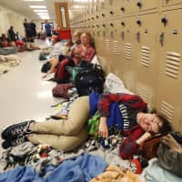 Emily Hindle lies on the floor at an evacuation shelter set up at Rutherford High School, in advance of Hurricane Michael's landfall in Panama City Beach, Florida, Wednesday. | AP