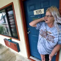 Rachel Ellison stands in the doorway of her apartment at the Lighthouse Motel, where she planned to ride out Hurricane Michael, in Panacea, Florida, Wednesday. | REUTERS