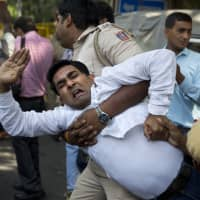 A policeman takes away a Congress party worker during a protest against Junior External Affairs Minister M.J. Akbar in New Delhi on Monday. | AP