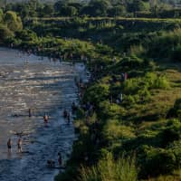 Central American refugees and asylum seekers bathe in Huixtla River in the town of Huixtla, Chiapas state, Mexico, on Tuesday. | BLOOMBERG