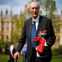 World War II Norwegian resistance fighter Joachim Roenneberg holds up a Union flag, which had been lowered from above the House of Lords, after it was presented to him by the Clerk of the House of Lords in Westminster, London, in 2013. | REUTERS