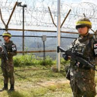 South Korean soldiers stand guard while removing land mines inside the Demilitarized Zone at the border with the North on Tuesday. | REUTERS