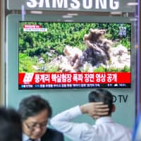 A man watches a television screen featuring a news report on the reported demolition of North Korea's Punggye-ri nuclear test site, at the main train station in Seoul in May. | BLOOMBERG