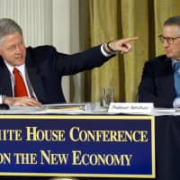 U.S. President Bill Clinton points to a guest as he sits next to Dr. William Nordhaus, then a professor of economics at Yale University, during the White House Conference on the New Economy in April 2000. The Nobel Prize in economic sciences was awarded to Nordhaus and Paul Romer on Monday. | AFP-JIJI