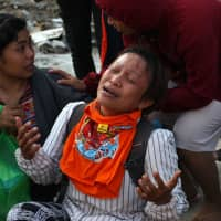 A woman grieves as she waits for an Indonesian rescue team searching for survivors at a collapsed building in Palu, Indonesia's Central Sulawesi, on Tuesday. | AFP-JIJI