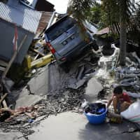 A boy sits with items salvaged from the ruins of a family member's house in the Balaroa neighborhood in Palu, Central Sulawesi, Indonesia, Tuesday. | AP