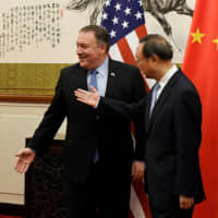Yang Jiechi, a member of the Political Bureau of the Chinese Communist Party, shows the way to U.S. Secretary of State Mike Pompeo before a meeting at the Diaoyutai State Guesthouse in Beijing on Monday. | POOL / VIA REUTERS
