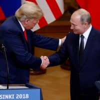 U.S. President Donald Trump and Russian President Vladimir Putin shake hands as they hold a joint news conference after their meeting in Helsinki in July. | REUTERS