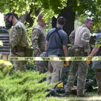 Law enforcement officers search a house on Wednesday in Logan, Utah. A man suspected of mailing ricin to the Pentagon and President Donald Trump was taken into custody at the scene. | ELI LUCERO / HERALD JOURNAL / VIA AP
