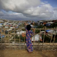 A Rohingya refugee girl stands by a fence at Kutupalong refugee camp, Bangladesh, in August. More than half a million Rohingya children live in the congested camps. | AP