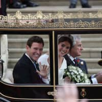 Britain's Princess Eugenie of York and her husband Jack Brooksbank get into the Scottish State Coach at the start of their carriage procession following their wedding at St. George's Chapel, Windsor Castle, in Windsor on Friday. | AFP-JIJI
