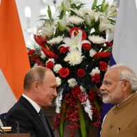 Russian President Vladimir Putin and Indian Prime Minister Narendra Modi shake hands after delivering a joint statement following their talks at Hyderabad House in New Delhi on Friday. | REUTERS