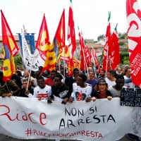 Migrants demonstrate in support of Mayor Domenico Lucano in front of his house in the southern Italian town of Riace, Oct. 6. The banner reads: 'You can't arrest Riace.' | REUTERS