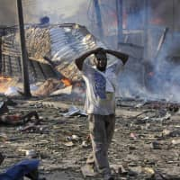 A man walks past a dead body and destroyed buildings at the scene of a blast in the capital Mogadishu on Oct. 14, 2017. Somalia is marking the first anniversary of one of the world's deadliest attacks since 9/11, a truck bombing in the heart of Mogadishu that killed well over 500 people. The Oct. 14, 2017 attack was so devastating that the al-Shabab extremist group that often targets the capital never claimed responsibility amid the local outrage. | AP
