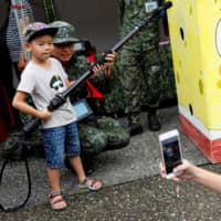 At a public fair displaying military equipment held in Taipei on Sept. 29, a child is seen posing with a soldier.   REUTERS