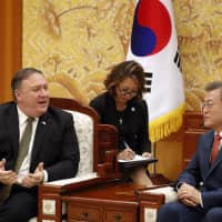 U.S. Secretary of State Mike Pompeo talks with South Korean President Moon Jae-in (left) during their meeting at the presidential Blue House in Seoul, Sunday. | KIM HONG-JI / POOL PHOTO / VIA AP