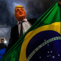A supporter of Jair Bolsonaro wears a mask of U.S. President Donald Trump as he celebrates the results of Brazil's presidential election in Sao Paulo on Sunday. | AFP-JIJI