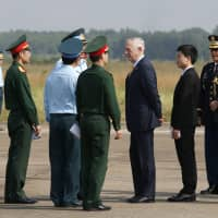 U.S. Defense Secretary Jim Mattis (third, right) talks with Vietnamese military officials while he visits Bien Hoa air base in Bien Hoa, outside Ho Chi Minh City, Vietnam, Wednesday. Mattis visited the air base that was heavily contaminated in the late 1960s and early 1970s by American forces through storage and spillage of the chemical defoliant Agent Orange. | KHAM / POOL PHOTO / VIA AP