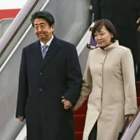 Prime Minister Shinzo Abe and his wife Akie arrive at the Beijing International Airport on Thursday. | KYODO