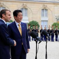 French President Emmanuel Macron (left) and Prime Minister Shinzo Abe pose for a photo in the courtyard of the Elysee Palace in Paris Wednesday. | REUTERS
