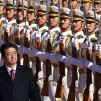 Prime Minister Shinzo Abe reviews a military honor guard during a welcome ceremony outside the Great Hall of the People in Beijing on Friday. | AFP-JIJI