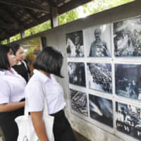 Visitors view photos from World War II at an exhibition inside Dusit Zoo in Bangkok, where a wartime air raid shelter is preserved, on Aug. 16. | KYODO