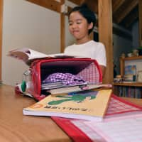 Fuku Kutsuwa, a fourth grader at Gifu Elementary School in the city of Gifu, shows off her school backpack, which has become much lighter to carry around, after the school recently allowed its students to keep their textbooks and other study materials at school.   CHUNICHI SHIMBUN