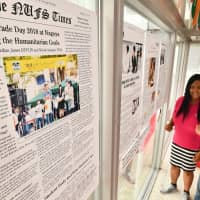 Cassandra Evangelista (right) looks at enlarged pages of an English-language newspaper on display at Nagoya University of Foreign Studies in Nisshin, Aichi Prefecture. | CHUNICHI SHIMBUN
