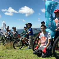 Hayate Endo (second from right) works as a mountain biking course guide for elementary school children in the Inabu district of Toyota, Aichi Prefecture, in August. | CHUNICHI SHIMBUN