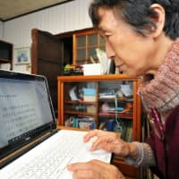 Mieko Hattori uses a computer at her home in Nagoya to write a story for children with the aim to eliminate gun deaths in the United States. | CHUNICHI SHIMBUN