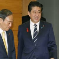Prime Minister Shinzo Abe and Chief Cabinet Secretary Yoshihide Suga gather for a Cabinet meeting Thursday. | KYODO