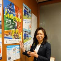 Michiyo Yakushiji, an independent Upper House lawmaker, stands by a poster publicizing the Deaflympics at her office in Tokyo on Sept. 26. | MIYA TANAKA
