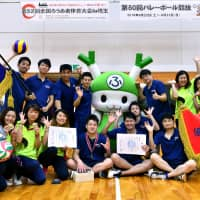 Winners of the men and women volleyball teams, both from Hyogo Prefecture, smile following an athletic meet for deaf people on Sept. 23 in the city of Fukaya, Saitama Prefecture. | YOSHIAKI MIURA