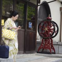 This photo by Jana Ontkova, the spouse of a diplomat in the Slovak Embassy, of a woman in a kimono looking at a smartphone, titled 'Harmony of Tradition with the Mobile,' won the Grand Prize at the 21st Japan through Diplomats' Eyes photo competition. | JANA ONTKOVA