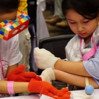 Girls experience life as a person with autism (left) or with a disability affecting the forearms and hands (right) through a game-like experience at the Lives Tokyo event in September at the Tokyo Midtown complex in Minato Ward. | MAGDALENA OSUMI