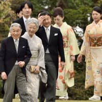 Emperor Akihito (left), Empress Michiko (second from left) and other members of the Imperial family make their way to greet guests during the annual autumn garden party at the Akasaka Palace Imperial garden in Tokyo in 2014. | AFP-JIJI