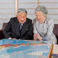 Empress Michiko looks at map of Japan with Emperor Akihito at the Imperial Palace in Tokyo on Oct. 10. The Empress celebrated her 84th birthday on Saturday. | REUTERS