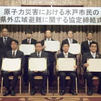 Mayor Yasushi Takahashi (front row, second from right) of Mito, Ibaraki Prefecture, poses for a photo with officials from six cities in Chiba Prefecture after signing an nuclear accident evacuation accord in the Chiba village of Kashiwa, on Wednesday. | KYODO