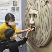 Visitors to Osaka University Hospital put their hands into a sanitizer dispenser that is shaped like the famous Roman sculpture the 'Mouth of Truth' on Tuesday. | KYODO