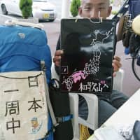 Junya Hida, a captured fugitive who was on the run for seven weeks from mid-August, holds a sign saying 'Wakayama' at a roadside rest area in Suo-Oshima, Yamaguchi Prefecture, in a provided photo taken on Sept. 18. Another sign next to him reads 'Cycling around Japan.' | KYODO