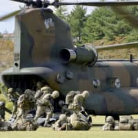 Ground Self-Defense Force and British Army personnel disembark a helicopter during a joint drill at the GSDF's training school in Shizuoka Prefecture on Tuesday. | KYODO