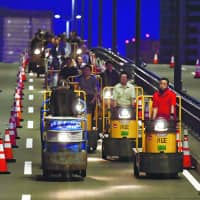 A convoy of electric carts and forklifts make the 2.3-kilometer-long journey from the closed Tsukiji fish market to the new Toyosu fish market in east Tokyo early on Sunday. Some 2,600 of the vehicles will eventually make the trip. The Toyosu market is scheduled to open Thursday. | KYODO