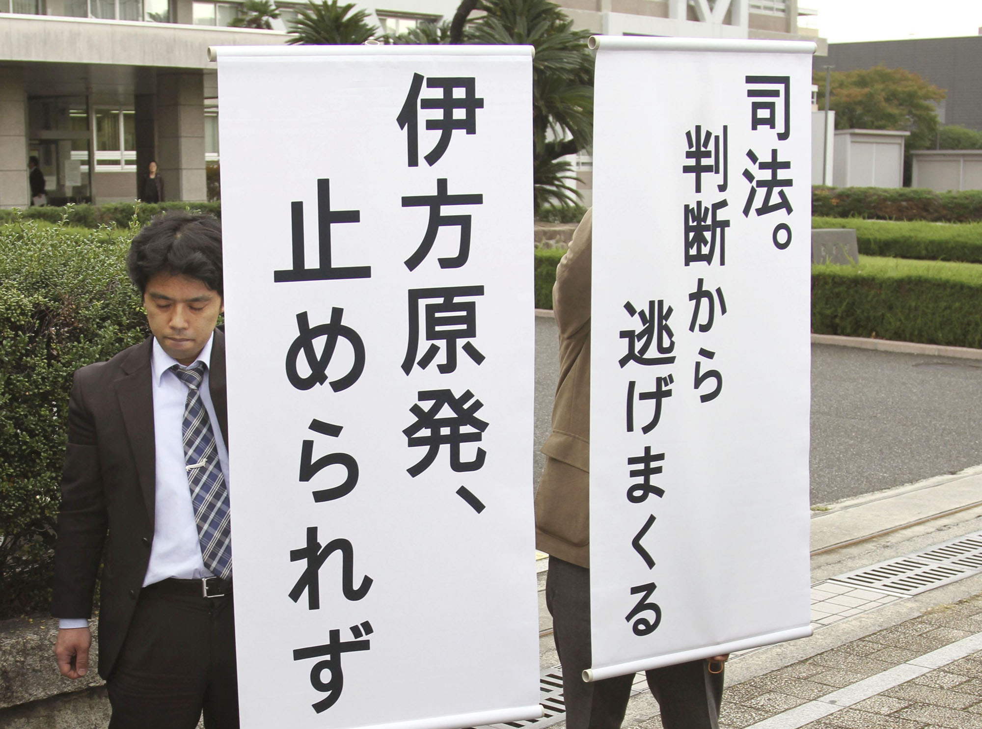 Signs saying 'Ikata nuclear power plant will not be suspended' and 'Judicial power that is shy of handing down judgements' are displayed in front of the Hiroshima District Court on Friday after the court rejected a call from residents to maintain the suspension of the plant. | KYODO