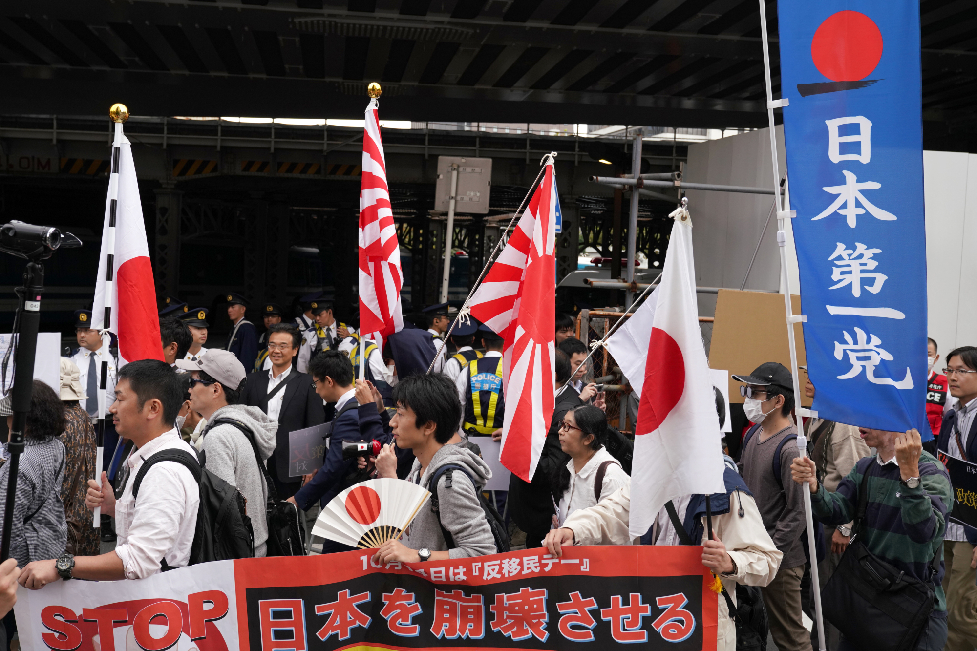 Demonstrators wave flags as they march during a rally against Prime Minister Shinzo Abe's proposed legislation regarding foreign workers in Tokyo on Sunday. The Japanese government submitted an outline to a panel of ministers on Friday in a step toward admitting more foreign workers amid a worsening labor shortage. | BLOOMBERG