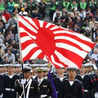 The flag of the Maritime Self-Defense Force is displayed during a military review at the Ground Self-Defense Force's Asaka base in Asaka, Saitama Prefecture, on Oct. 14. | AFP-JIJI