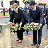 Foreign Minister Taro Kono and Australian Foreign Minister Marise Payne lay wreaths at HMAS Kuttabul in Sydney on Wednesday. | AP