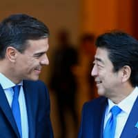 Spanish Prime Minister Pedro Sanchez welcomes Prime Minister Shinzo Abe on Tuesday at his office in the Moncloa Palace in Madrid. | AFP-JIJI
