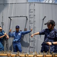 A female navigator (right) of the Japanese helicopter carrier Kaga prepares to practice raising signal flags in the Indian Ocean off Indonesia Sept. 23. | REUTERS