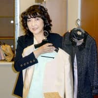 Satsuki Katayama on Tuesday shows two formal outfits she had prepared for the declaration ceremony for newly appointed ministers at Tokyo's Imperial Palace. Prior to the ceremony she learned the outfits did not suit the dress code. | KYODO